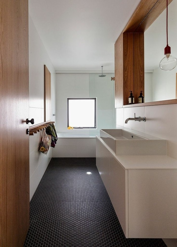 bathroom design ideas, black flooring and white walls with pale blue detail, white sink and cupboard, wooden door and details