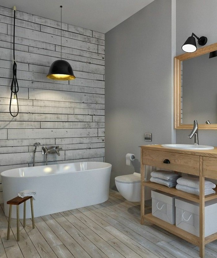 bathroom design ideas, pale wooden floor, one wall painted grey, opposite wall decorated with grayish-white wooden planks, white ceramic tub and sink