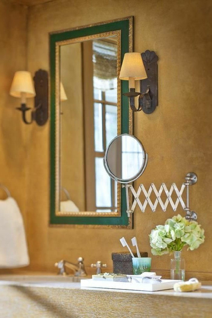 bathroom makeovers, sienna yellow wall, mirror in green frame, two wall lights, magnifying mirror near toothbrushes and flowers