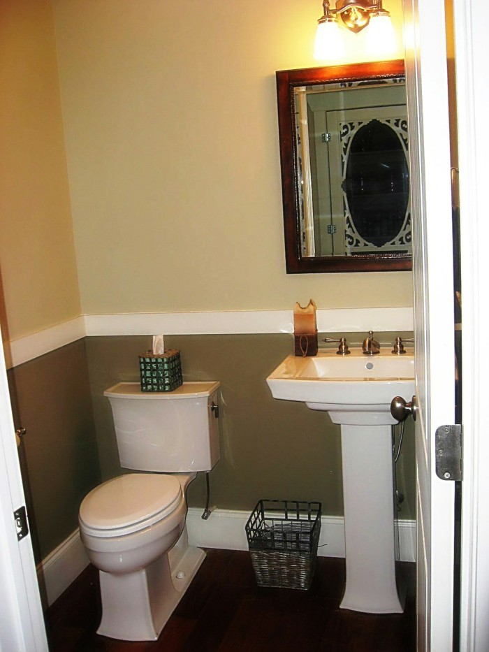 bathroom remodel, pale yellow and dark khaki walls with white detail, dark wooden floor, white ceramic toilet and sink, mirror in wooden frame