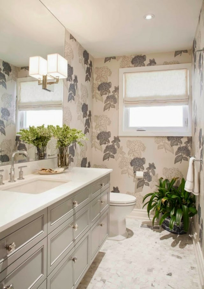bathroom design ideas, white cupboard with drawers and sink, big mirror with wall light, walls covered in a cream and brown wallpaper