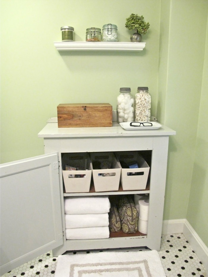 bathroom ideas photo gallery, pale green wall, floor with tiny black and white mosaic tiles, cream colored open cupboard, filled with toiletries