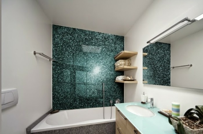 bathroom designs, inbuilt tub near a blue-green-shining wall-panel, white walls and a mirror