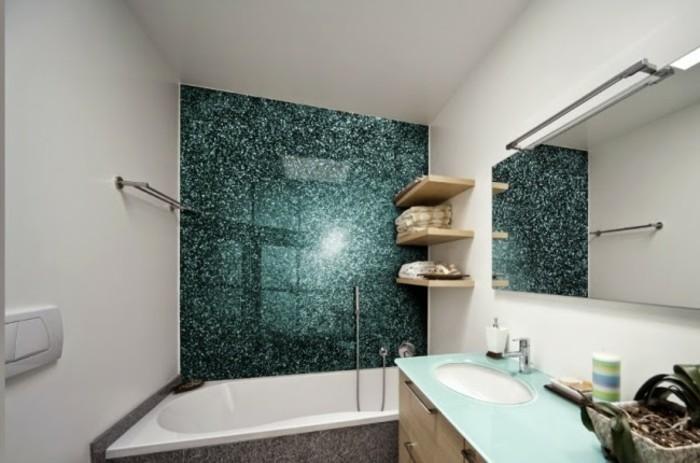 bathroom designs, inbuilt tub near a blue-green-shining wall-panel, white walls and a mirror