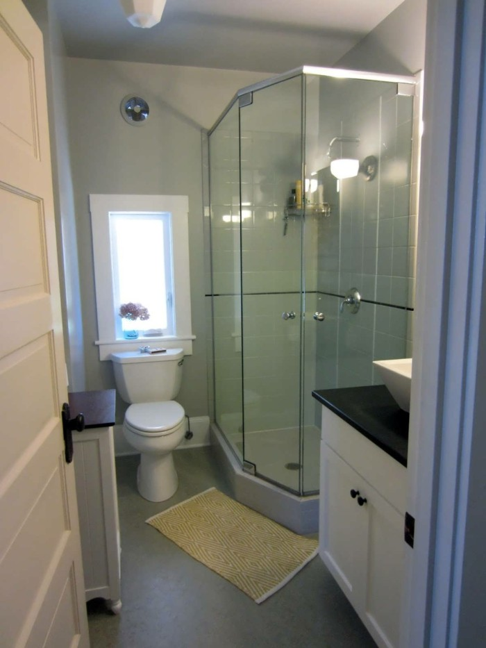 bathroom renovations, pale gray walls, glass shower cabin, white toilet and cupboards