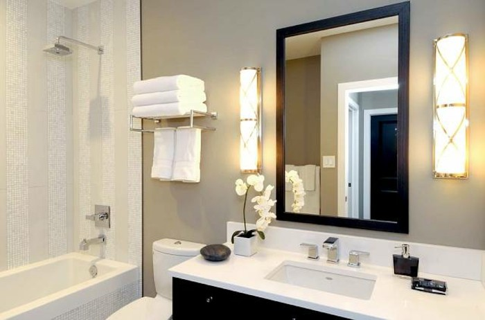 remodeling ideas, cream-colored wall with mirror in a dark frame, black cupboard with white sink, white and cream shower and bath area