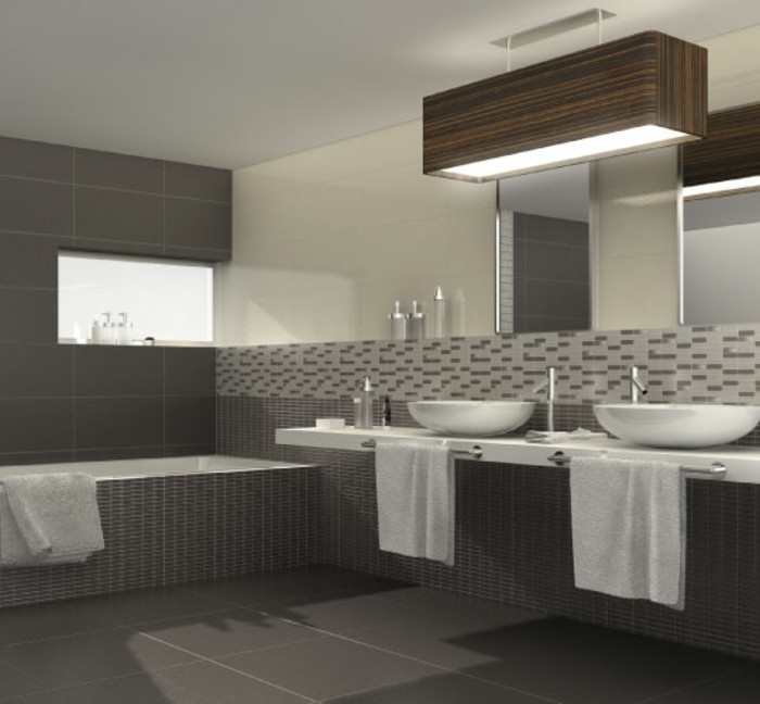 dark grey floor tiles, large wall mirror, two white sinks, inbuilt bath with dark grey mosaic, more mosaic tiles on wall, in different shades of grey
