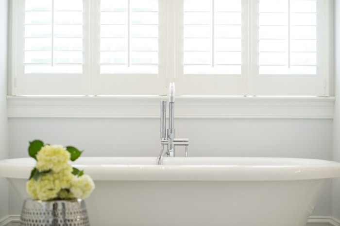 bathroom remodel ideas, white wall and window, white ceramic bath with metal tap, yellow flowers in metallic vase