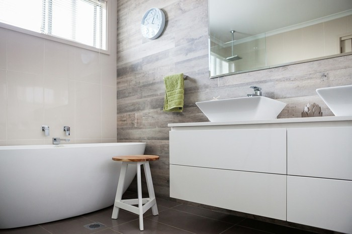 bathroom renovations, white ceramic tub, white cupboard with two ceramic sinks, brown tiled floor