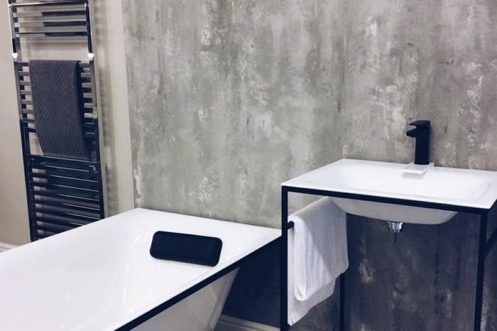 bathroom renovations, grey wash wall, white tub and sink, with black metal frames, metal towel rail
