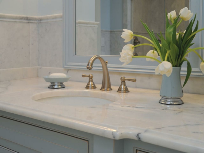 bathroom designs, close up of pale blue sink with marble top surface, yellow metallic taps, mirror and a vase with tulips