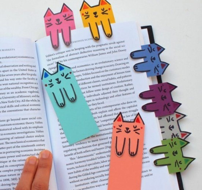 best friend gift ideas, hand holding open book, decorated with eight bookmarks in different colors, shaped like cats