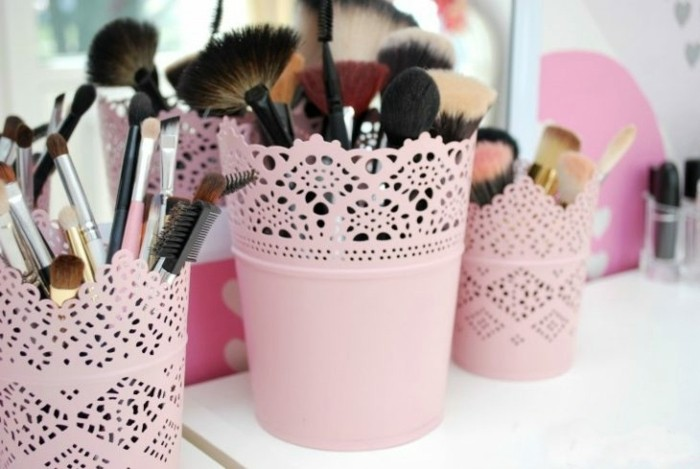 cool gifts for teens, three ornate pots painted in pale pastel pink, containing a wide variety of make-up brushes