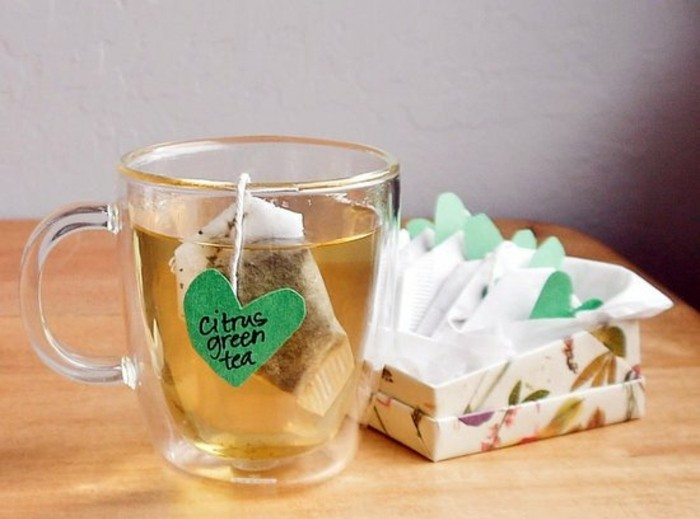 what to get your best friend for her birthday, clear glass mug, containing tea and a teabag, with handmade heart-shaped green label, more teabags in a box nearby