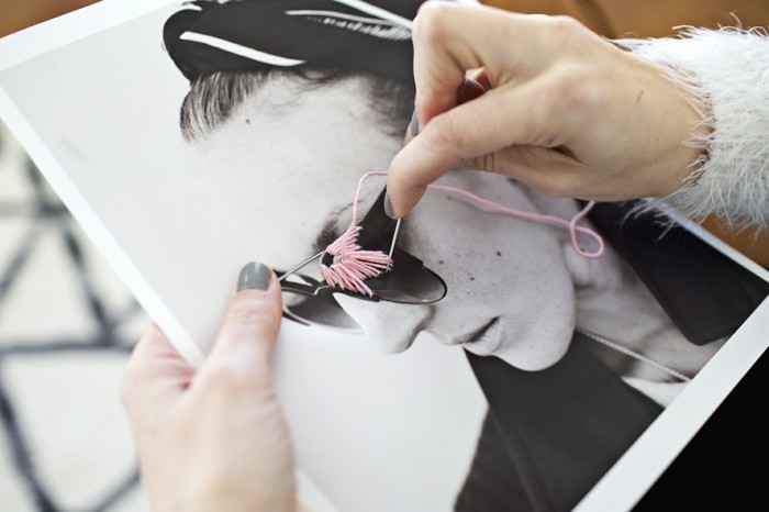 gifts for best friends, female hands holding black and white photo, and stitching pink thread onto it
