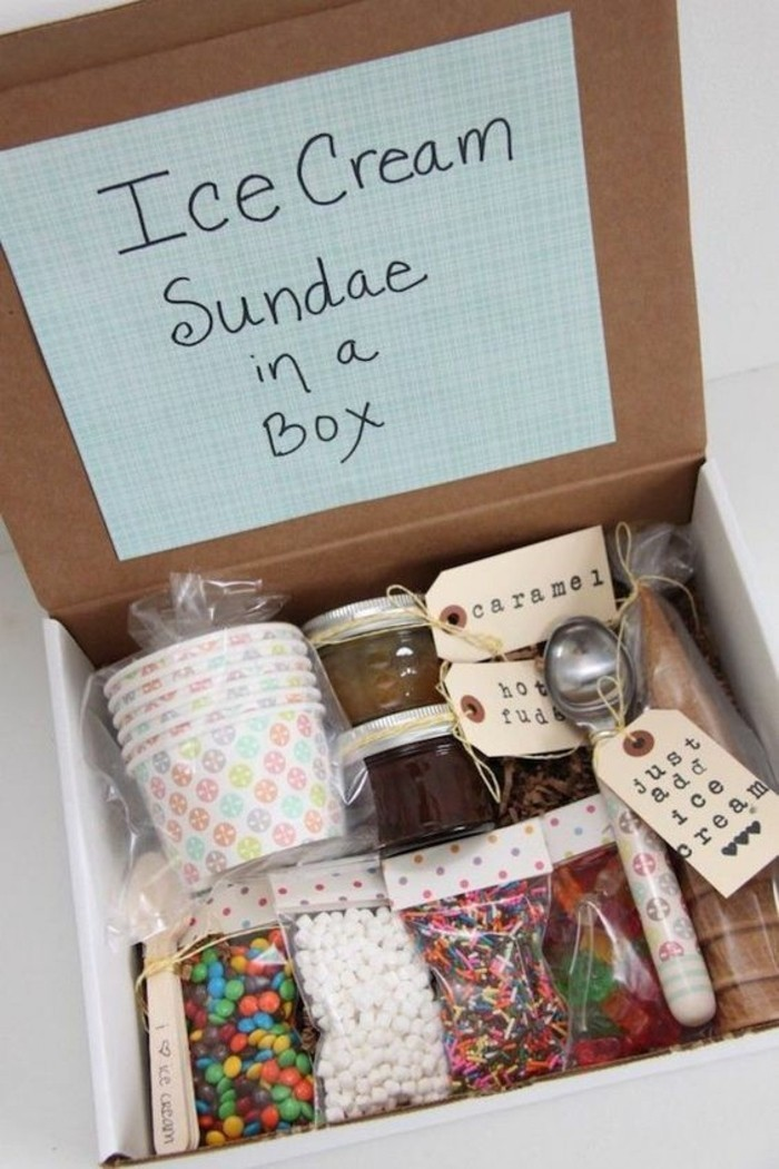 open cardboard box, containing plastic bags with ice cream cones, spoons and paper bowls, many different types of ice-cream toppings