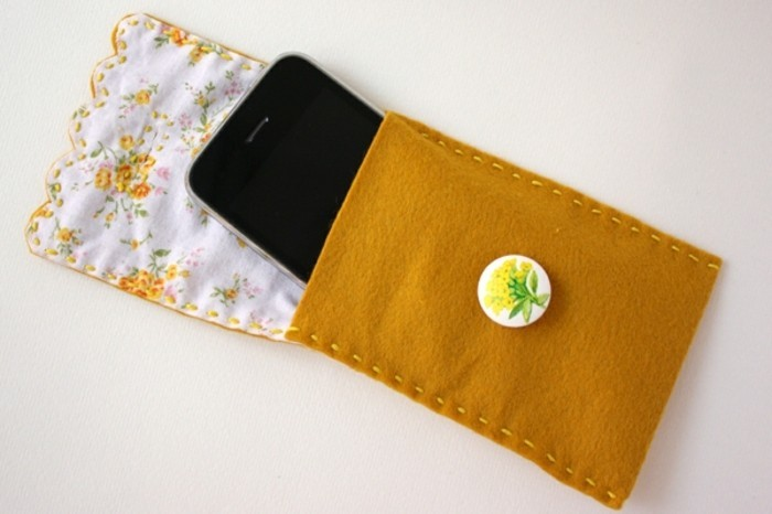 best friend christmas gifts, black smartphone inside a hand-stitched pocket, made from felt in mustard color, with white and yellow lining, and a flower pin decoration