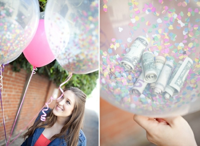 cool gifts for teens, smiling brunette woman, holding a pink balloon and two clear balloons filled with confetti, close up of one of the clear balloon reveals several rolled-up dollar bills inside