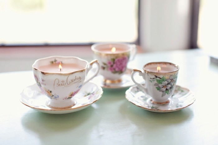 best friend christmas gifts, three painted porcelain cups and saucers, containing lit pink candles, on pale blue surface