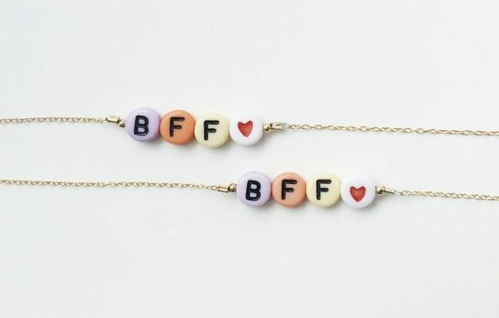gifts for best friends, close-up of two bracelets, thin gold-colored chains, decorated with colorful pebbles, with the letters BFF and a heart