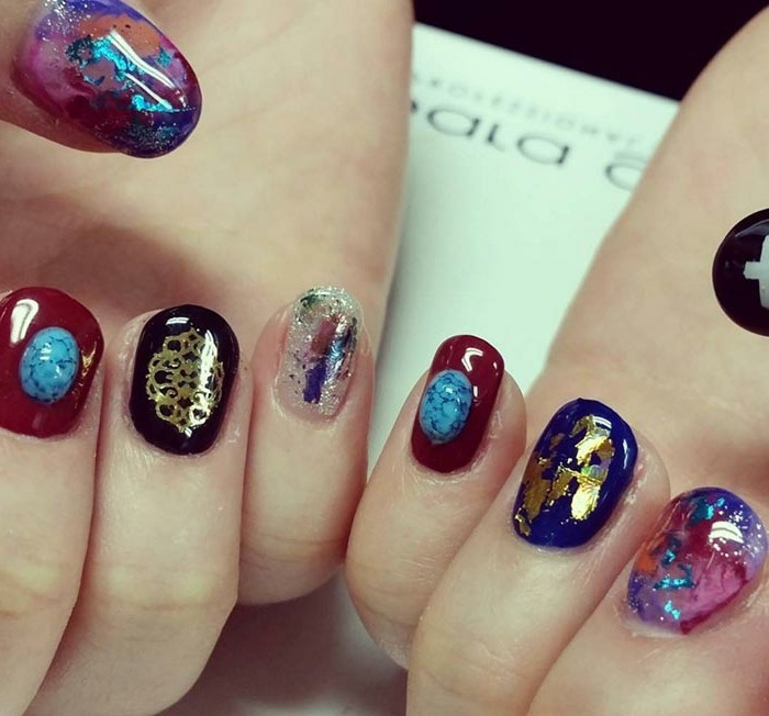 nail designs with rhinestones, extreme close up of two hands with multicolored nails, red with turquoise stones, black with gold details