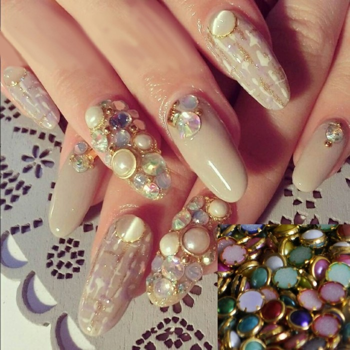 rhinestone nail designs, close up of long round nails, two decorated with several multicolored rhinestones, others with gold designs and less rhinestones