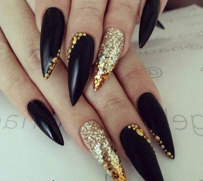 rhinestone nail art, long and sharp black nails with gold details, ring fingers' nails fully covered in golden glitter