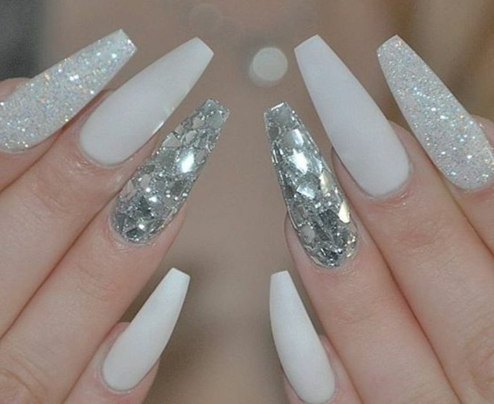 rhinestone nail designs, eight very sharp nails, painted with white nail polish, two nails covered in white glitter, another two decorated with shiny glittering shards