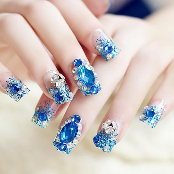 rhinestone nail art, close up on two hands, decorated with fake nails featuring big blue gems, white rhinestones and blue glitter