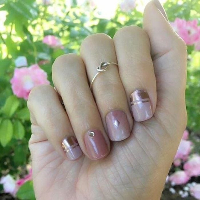 nail designs with rhinestones and glitter, close up of hand with short nails, painted in pastel and metallic pink, decorated with one rhinestone