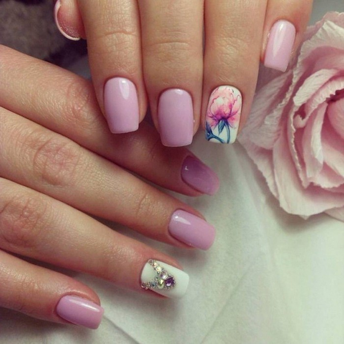 nails with rhinestones, close up of two hands, nails colored in pastel pink and white, one nail has a rhinestone decoration, one nail has a painted rose
