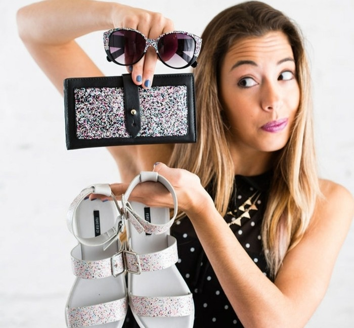 best friend gift ideas, blonde woman holding a pair of white sandals, sunglasses and a wallet, all decorated with confetti nail polish