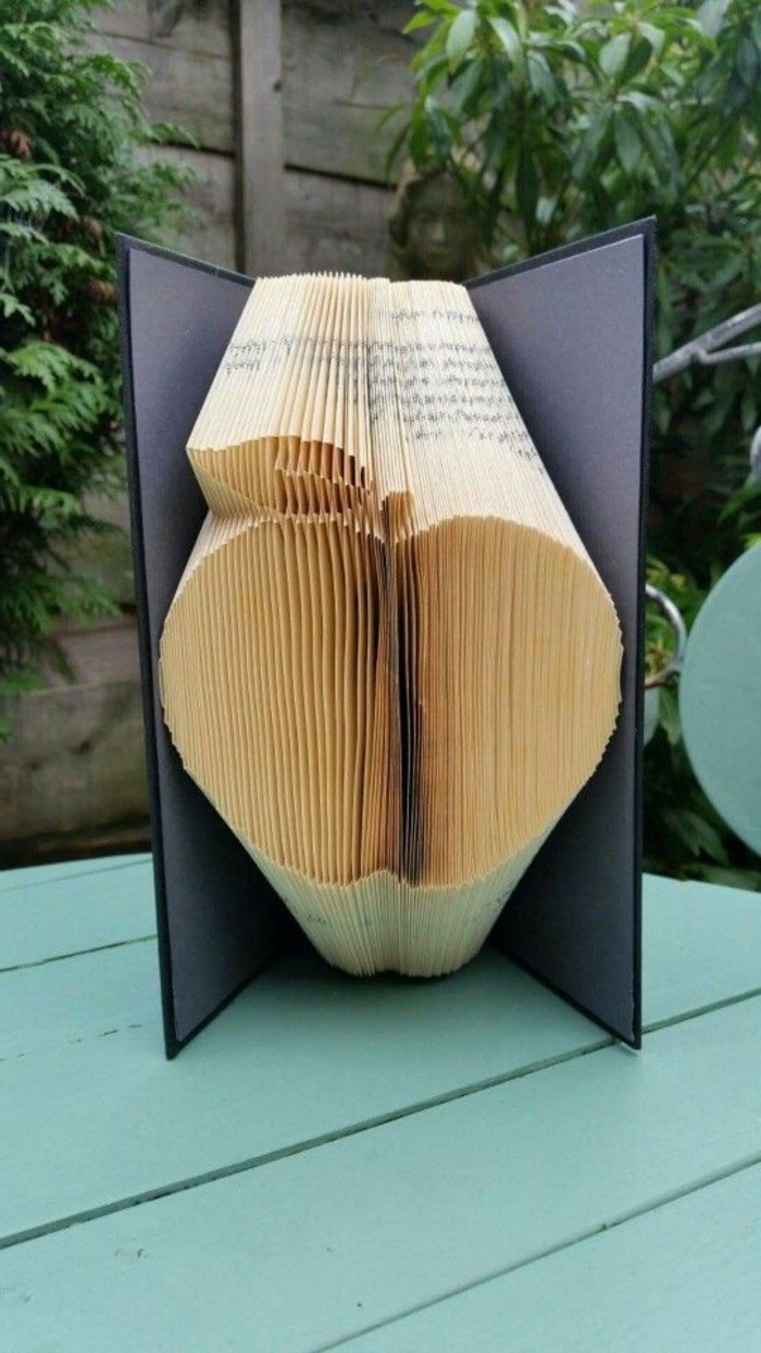 book folding, apple shape made from folded pages, inside an open book, with dark grey and black hard covers