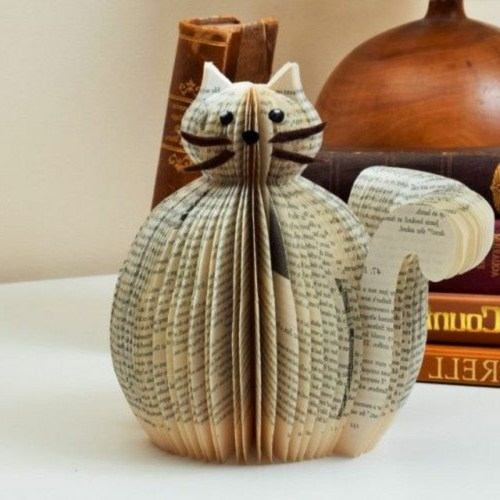 book folding art, cat figure made from cut and folded book pages, decorated with paper eyes and nose, and felt whiskers