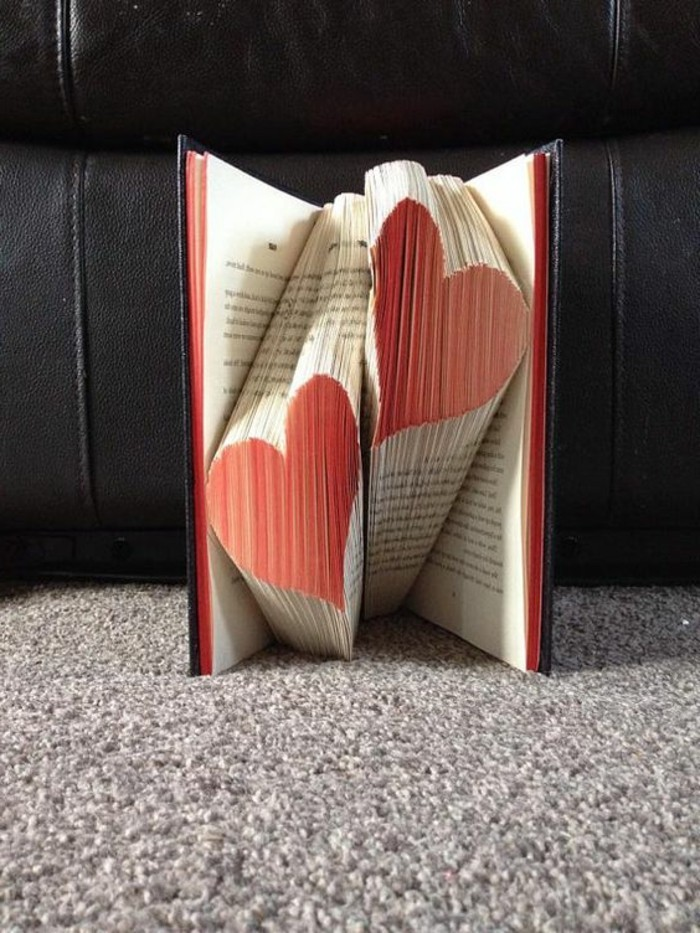 book folding art, two hearts made from folded pages, and painted red, inside an open book with black hard covers