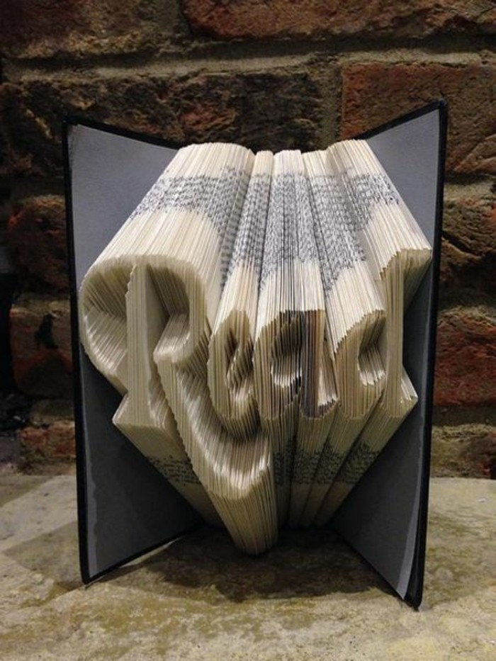book folding, opened book with grey and black hard covers, containing the word read in fancy writing, created from folded pages