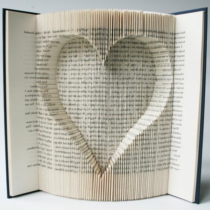 book folding, book with black hard covers, opened to reveal heart shape, made from cut and folded pages