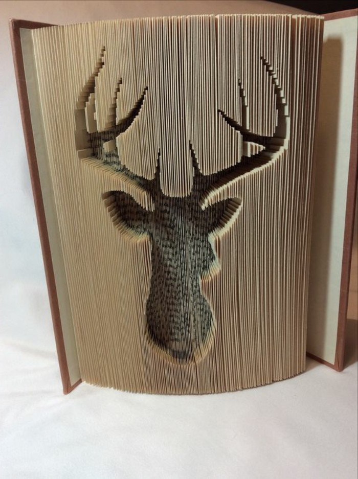 book folding patterns, semi-opened book, with hard brown covers, an elk-head shape carved into its pages