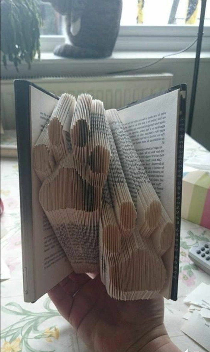 book folding patterns, two paw prints, made from folded pages, inside an open book, with hard dark covers, held by hand