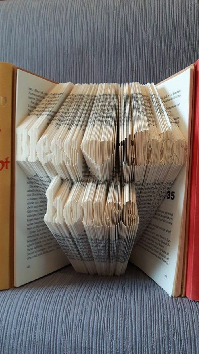 folded book art patterns, opened book containing the message bless this mess, and a heart shape, made from folded book pages