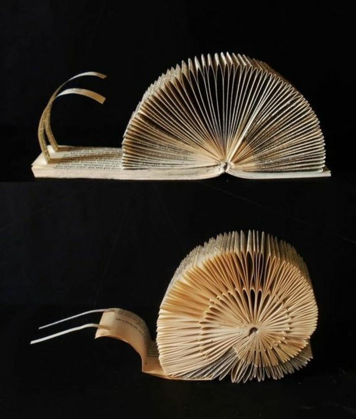 book folding patterns, two snail decorations, made from cut and folded book pages, placed on a black background