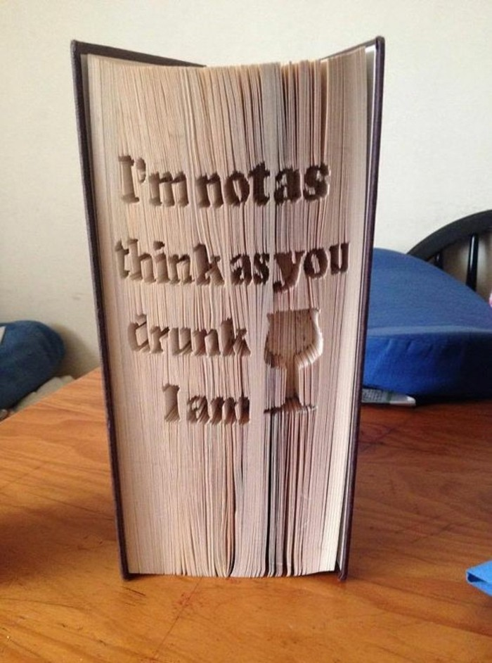 book folding, closed book with dark hard covers, with a long message, and a wine-glass shape, carved into its pages