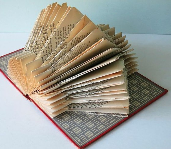 book folding, open book with red hard covers, featuring a grey and white pattern, displaying pages folded into a geometric, lantern-like shape
