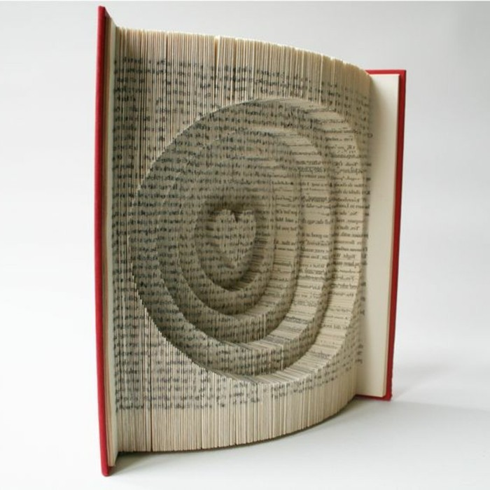 book with red hard covers, opened to reveal pages, folded to make several circles, with a heart shape in the middle