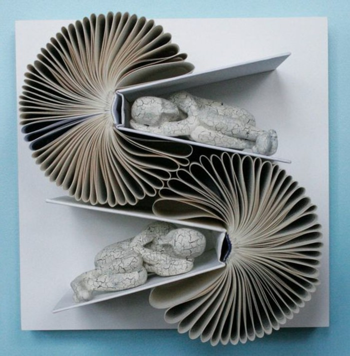 bookfolding, artwork made from two open books, stuck on a canvas, with folded pages, and two human figures made from cracked white stone, placed between the books' covers