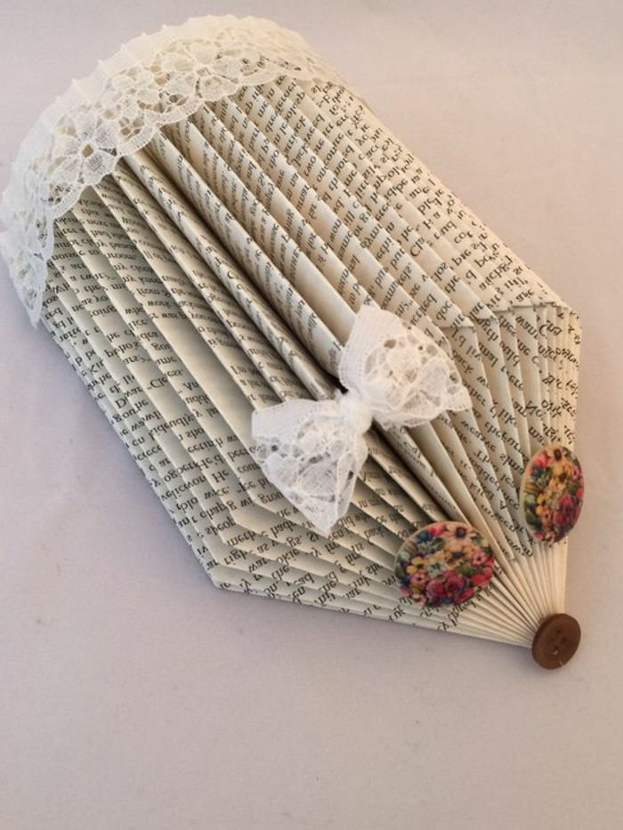 book folding art, hedgehog made from cut and folded book pages, decorated with lace trim and bow, with floral buttons for eyes, and a small brown button for nose