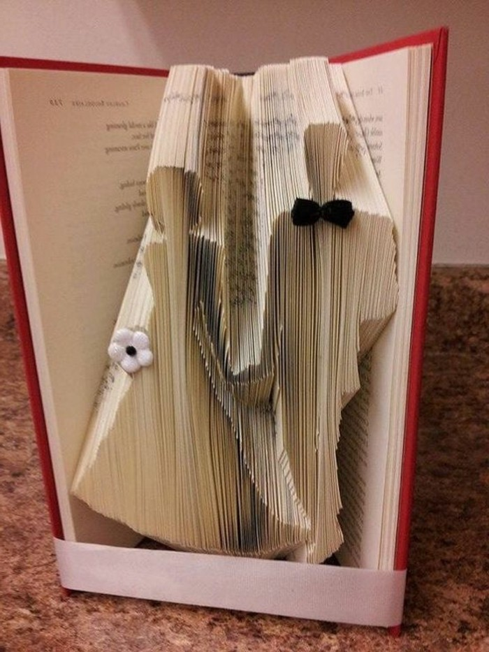 bookfolding, bride and groom holding hands, made from folded pages, decorated with small white flower and tiny black bowtie, inside an open book with hard red covers, tied with white ribbon
