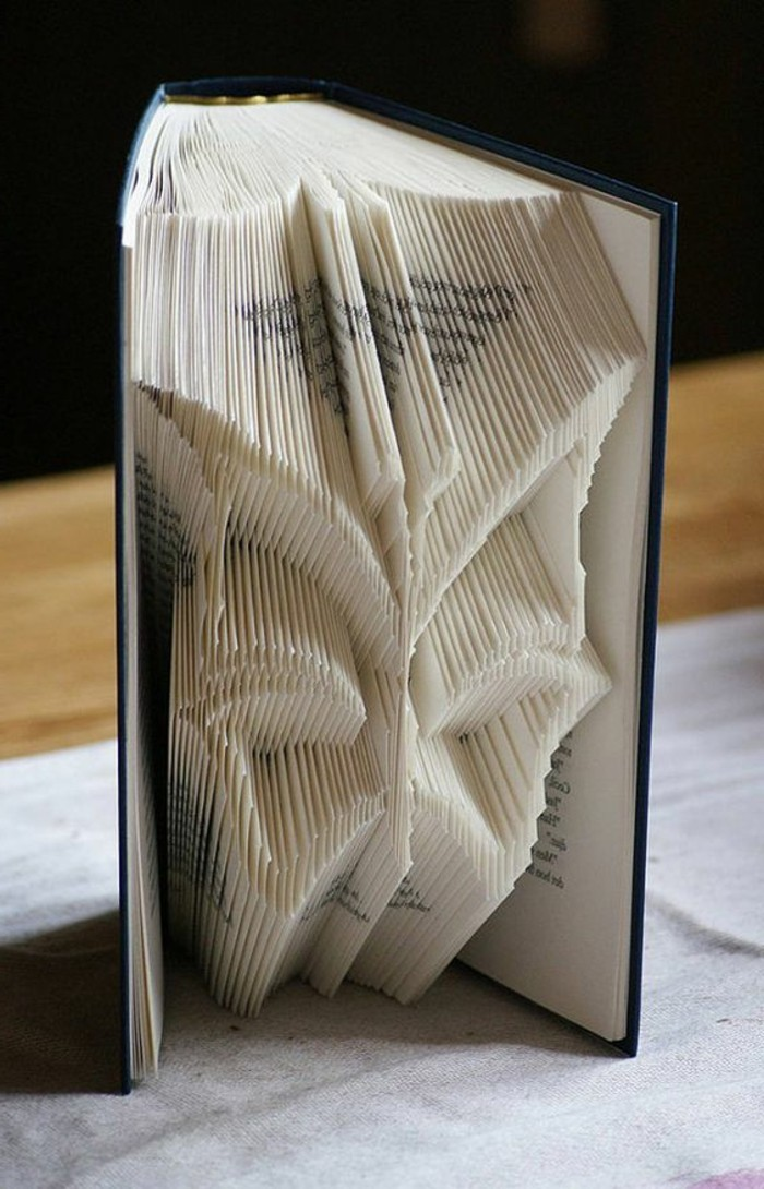 bookfolding, butterfly shape made from folded pages, inside an open book, with dark blue hard covers