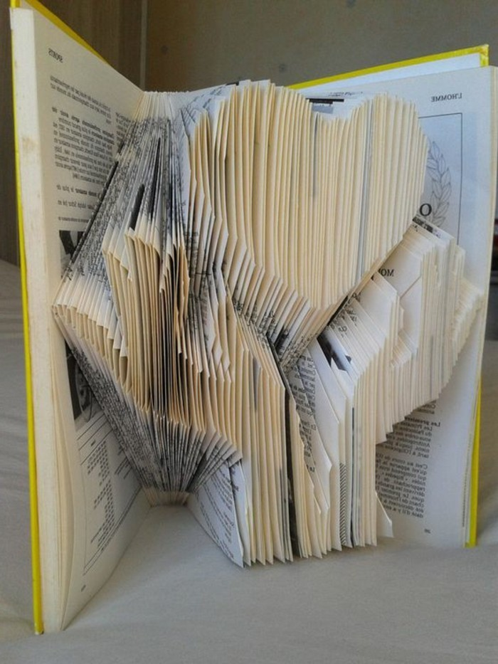bookfolding, 3D image of two hands, holding a heart shape, made from folded pages, inside an open book, with hard yellow covers