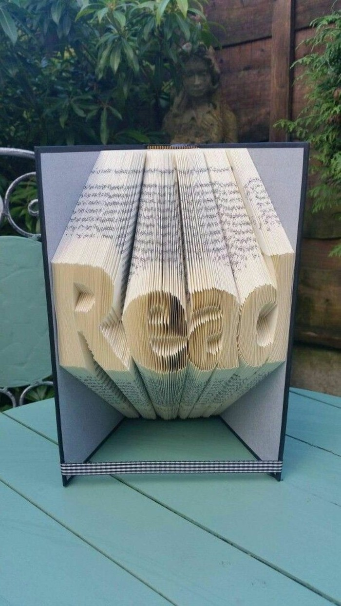 bookfolding, the word read, made from folded pages, inside a book with grey and black hard covers, tied with a chequered ribbon